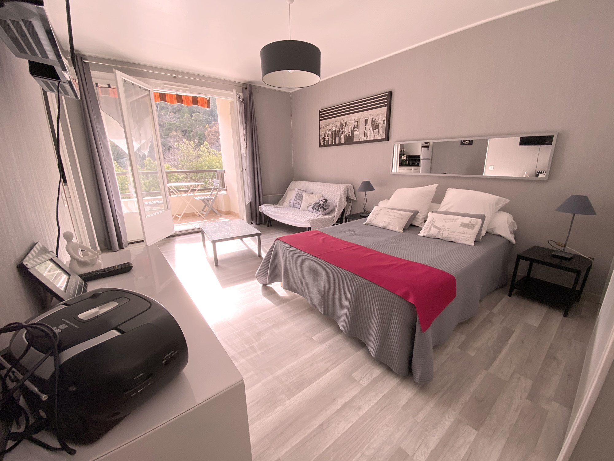 Chambre grise lit avec couverture rouge appartement Amelie les bains