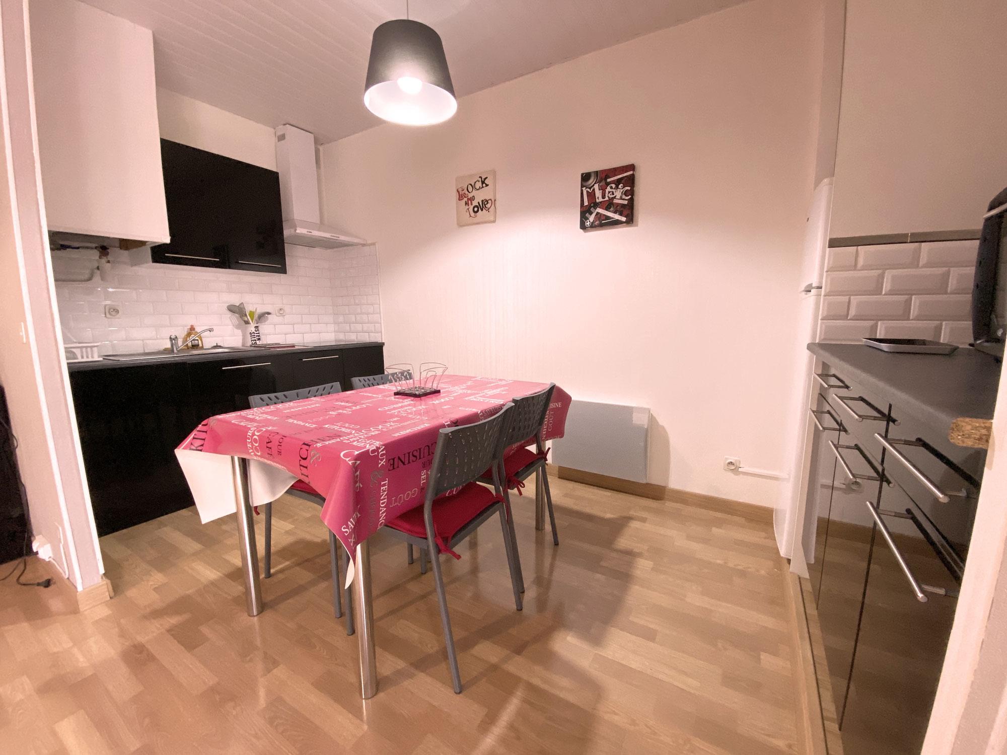Cuisine murs blanc ,élements noirs , table rouge