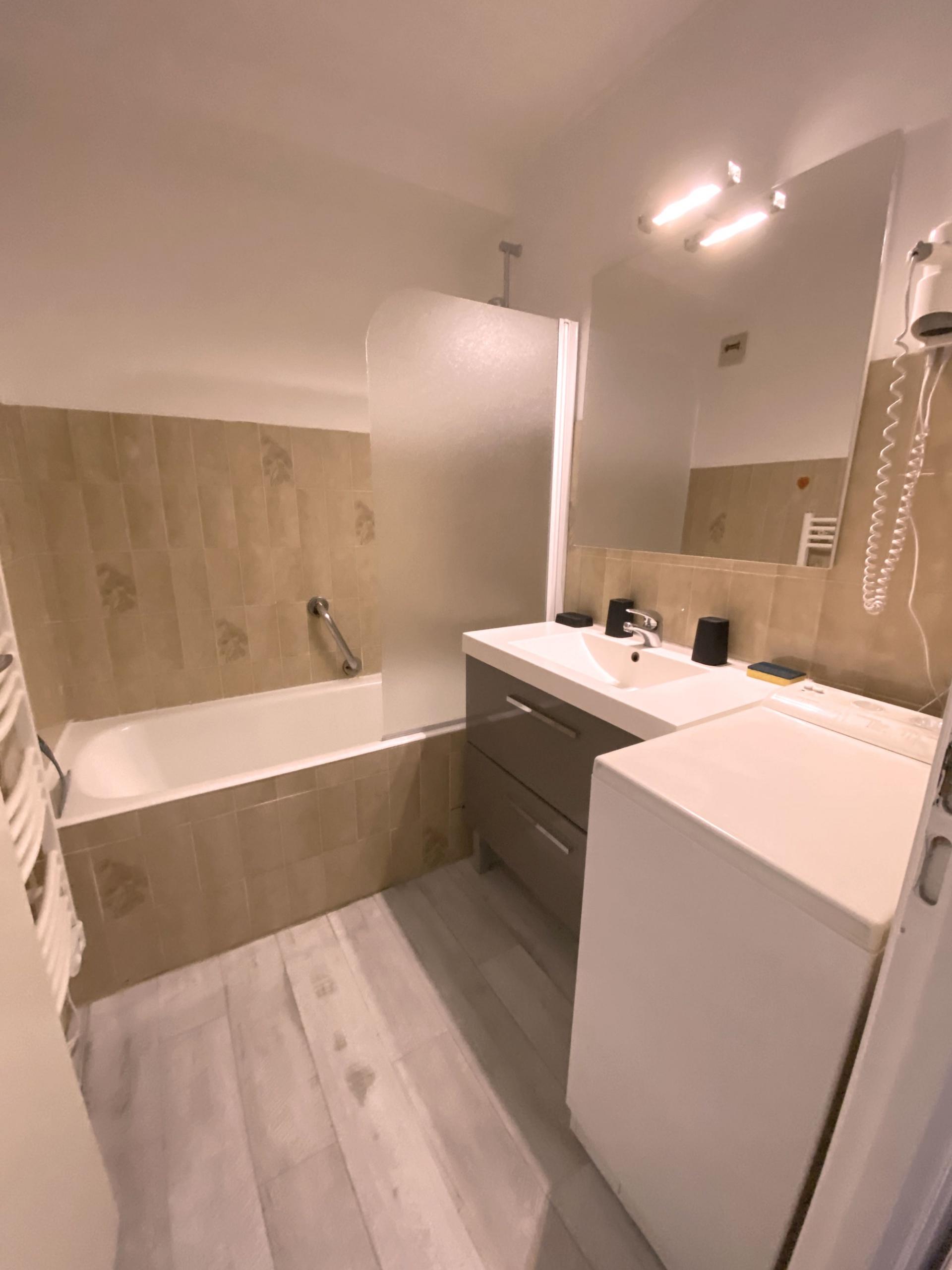 Salle de bain avec baignoire , lavabo , lave linge