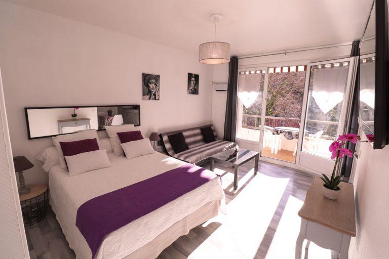 Vue d'un lit avec couverture violette