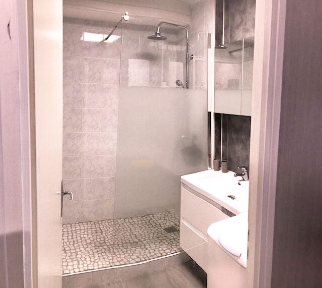 Salle d'eau avec douche à l'italienne rose et grise une machine à laver un lavabo