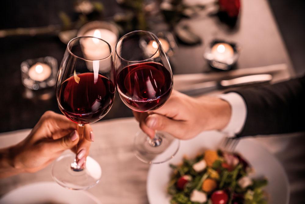 deux personnes avec des verres de vin dans un restaurant